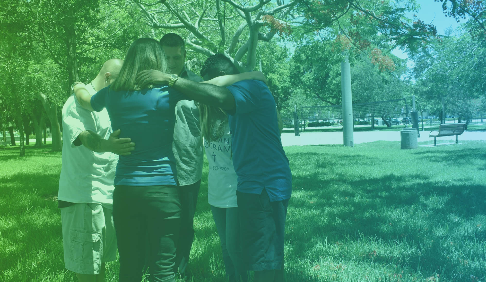 five people praying together at a park
