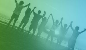 seven people hold their hands up at the beach