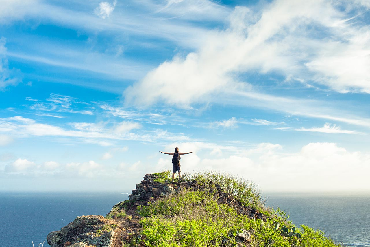 woman standing happily on ledge