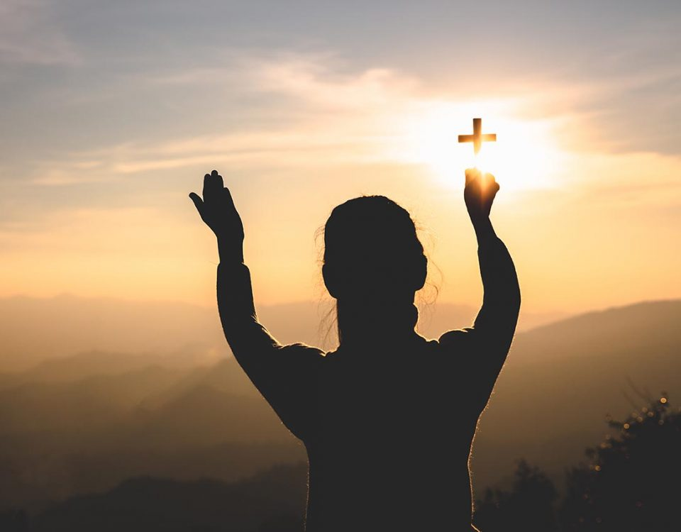 woman holding up a cross