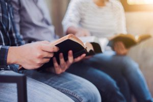 man and woman holding bibles