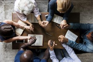 six people praying together at a wooden table